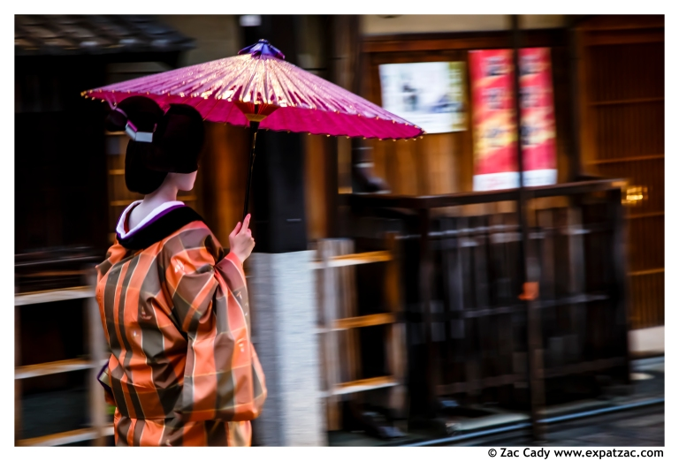 A Maiko makes her way along Hanami-kōji in the pouring rain of a tropical storm.
